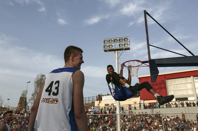 "Milwaukee Bucks' forward Giannis Antetokounmpo, right, smiles after scoring as New York Knicks star Kristaps Porzingis looks on during a friendly game in Athens, on Sunday, May 29, 2016. Porzingis joined fellow NBA player Giannis Antetokounmpo, of the Milwaukee Bucks, and his older brother Thanasis, for a game of streetball Sunday. The ""Antetokounbros Streetball Event,"" organized by Eurohoops and the City of Athens, took place in an open court, at Greece's largest high school, and attended by 5,000 people. (AP Photo/Yorgos Karahalis)"